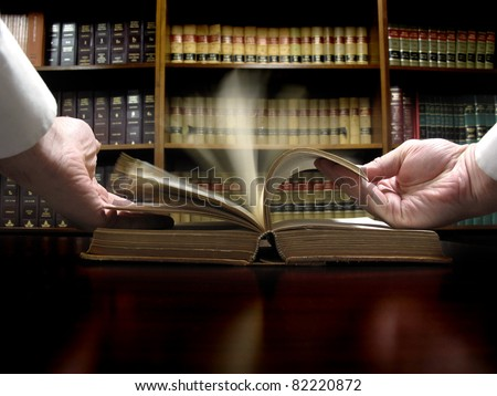 Hands turning pages in old law book with library in background