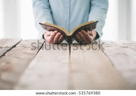 Hands turning the page of a bible