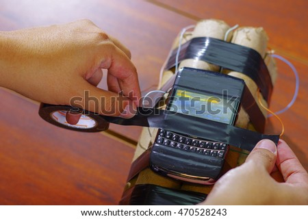 hands tying the caellphone with tape to a set of explosives #470528243
