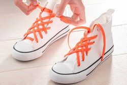 Hands tying white sneakers with orange shoelaces. Make plain shoes look cool with lattice lace.