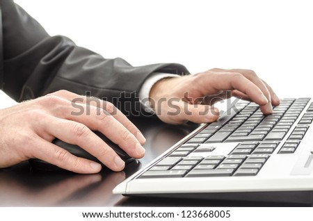 Hands typing on computer keyboard on  a black desk.