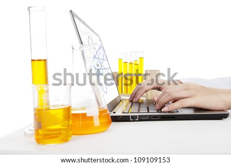 Hands typing on laptop computer doing an experiment of chemical particle