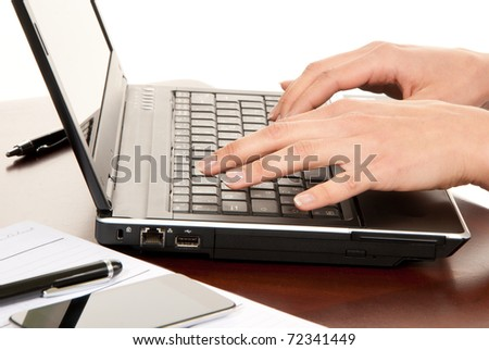 Hands typing on laptop computer keyboard in an office at a workplace near notebook, pen, cellphone isolated on a white background