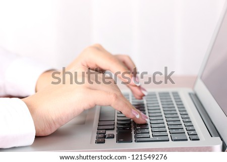 Hands typing on laptop keyboard close up