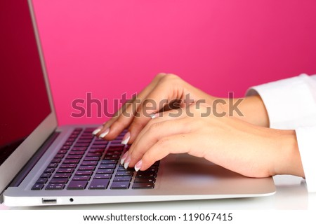 Hands typing on laptop keyboard close up on pink