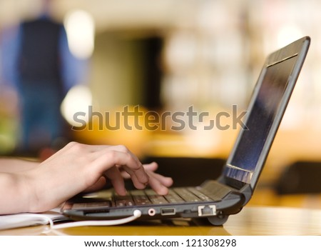 Hands typing on notebook in college class