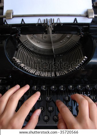 Hands typing on old typewriter