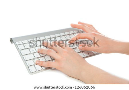 Hands typing on the remote wireless computer keyboard in an office at  workplace isolated on a white background