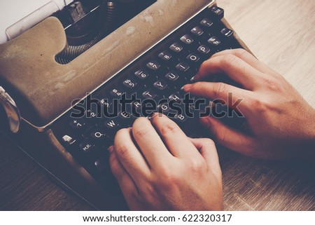 Hands typing on vintage typewriter on wooden table. #622320317