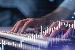 Hands typing the keyboard to research stock market to proceed right investment solutions. Internet trading and wealth management concept. Hologram Forex chart over close up shot.