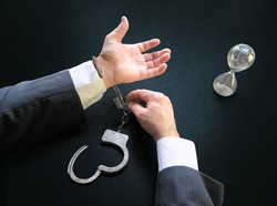 Hands unfasten the handcuffs. Open handcuffs on the male hands of the arrested person. Acquittal of an innocent defendant , a businessman in a black suit. Termination of criminal prosecution.
