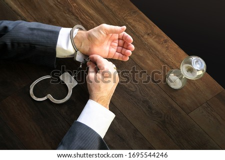 Hands unfasten the handcuffs. Open handcuffs on the male hands of the arrested person. Acquittal of an innocent defendant , a businessman in a black suit. Termination of criminal prosecution.          Stock photo ©
