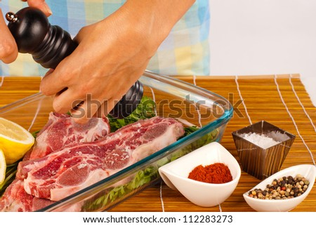 Hands using a pepper grinder to season raw meat