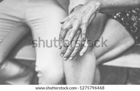 Hands view of senior couple having tender moments outdoor - Mature people outside sitting in a bench - Love, vintage and joyful elderly active lifestyle concept - Focus on woman hand  #1275796468