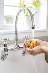 Hands washing fresh cherry tomatoes in running water of kitchen sink with curved faucet