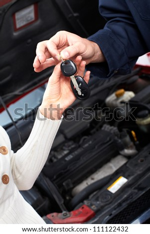 Hands with a Car keys. Auto repair service.