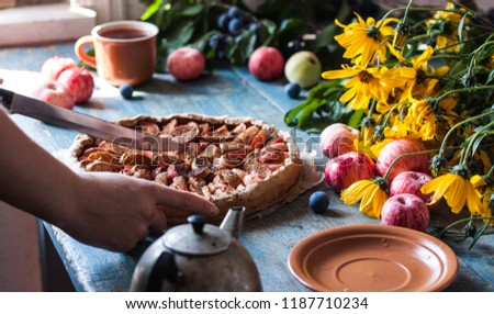 Hands with apple pie on wooden blue rustic background. Hello autumn picture. Apples, yellow flowers and plums.