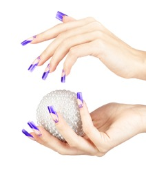 Hands with blue french false acrylic nails manicure holding perl christmas ball isolated on white background