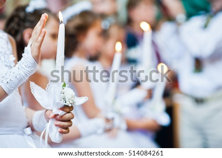 Hands with candles of little girls on first holy communion #514084261