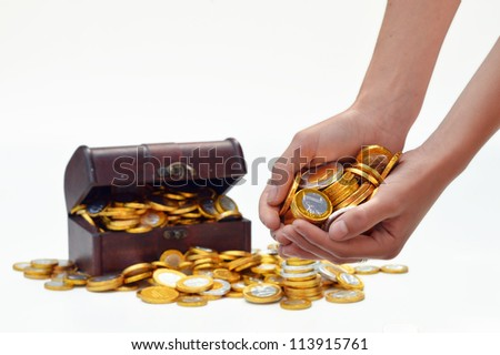 Hands with chocolate candy euro coins and a treasure chest in the background.