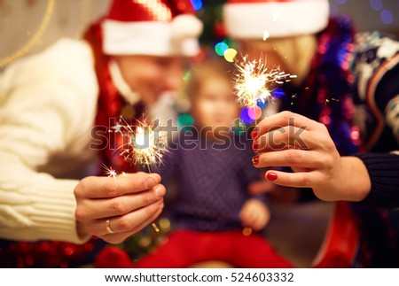 Hands with christmas sparklers. Beautiful family holding sparklers in their hands.    #524603332
