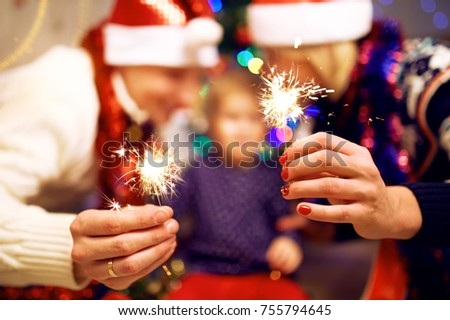 Hands with christmas sparklers. Beautiful family holding sparklers in their hands.  young people laugh. celebrating New Year together. Blur Background   #755794645