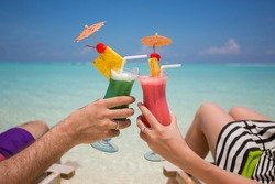 Hands with colorful cocktails on the beach.