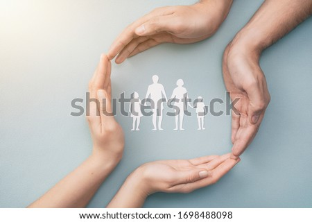 Hands with cut out paper silhouette on table. Family care concept.