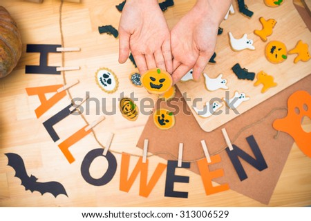 Hands with decorated Halloween cookies, view from above #313006529