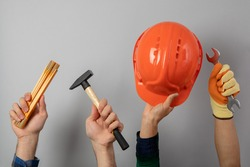 Hands with different construction tools on gray background