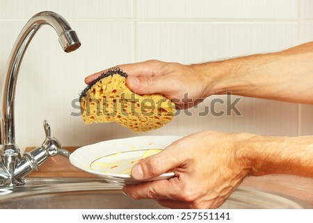 Hands with dirty dishes over the sink in the kitchen