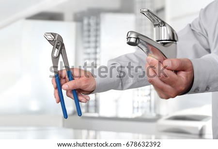 Hands with faucet and pipe wrench, install and construction home services plumber concept #678632392