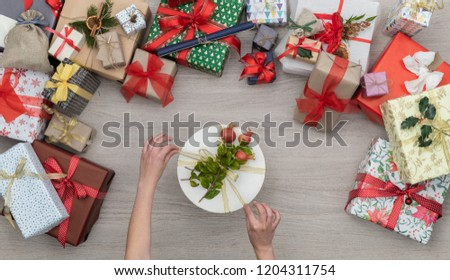 Hands with gift present box in vertical top view wooden table full of christmas or birthday gifts presents.Xmas winter holiday season party social media card background,portrait story