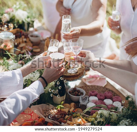 hands with glasses of white wine or champagne. people raised their glasses at the picnic table. friends clinking glasses with wine