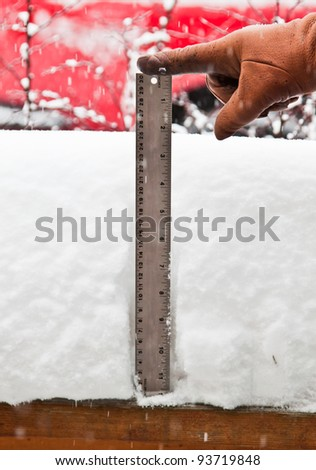 hands with gloves measuring the snowfall with a ruler
