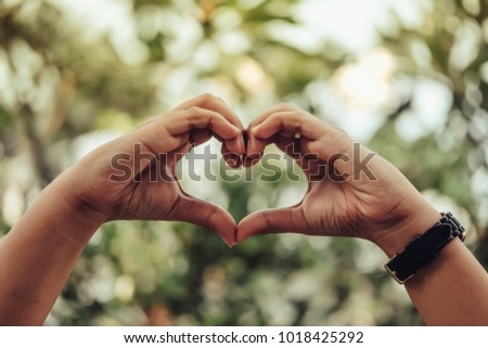 Hands with heart sign on green blur at garden background. Love concept #1018425292