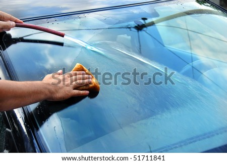hands with hose and sponge washing blue car glass