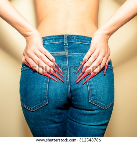 Hands with long red nails on the buttocks in jeans. Young woman with  gel nails manicure holding hand at jeans back