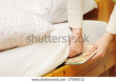 Hands with money hide them under mattress - stock photo
