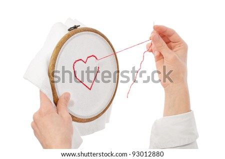 hands with needle embroidering red heart on white canvas