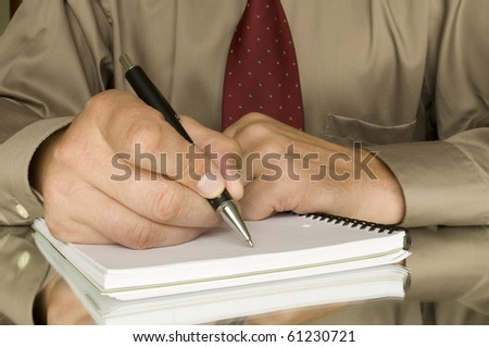 hands with pen writing on the notebook and reflection