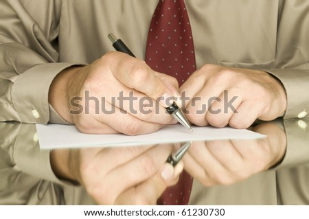 hands with pen writing on the white page and reflection