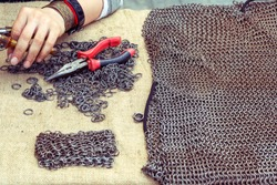 hands with pliers. chain mail. handwork. making medieval armor