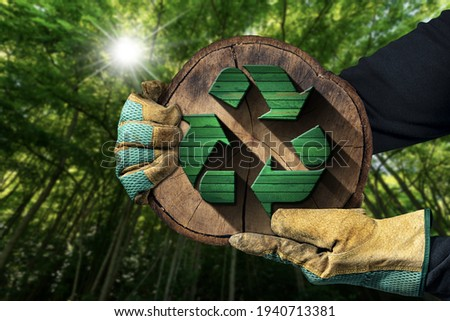 Hands with protective work gloves holding a recycling symbol made of green and brown wood inside of a cross section of a tree trunk. Sustainable Resources concept. Green forest on background.