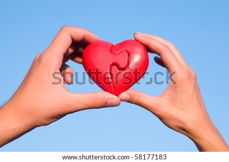 Hands with puzzle heart in sky