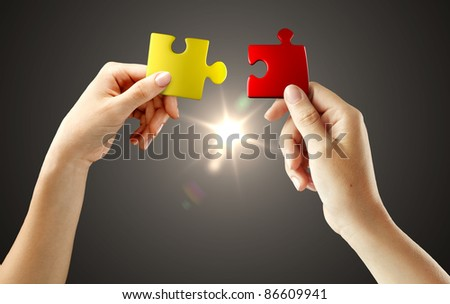 Hands with puzzle on black background. Teamwork solving a puzzle - stock photo
