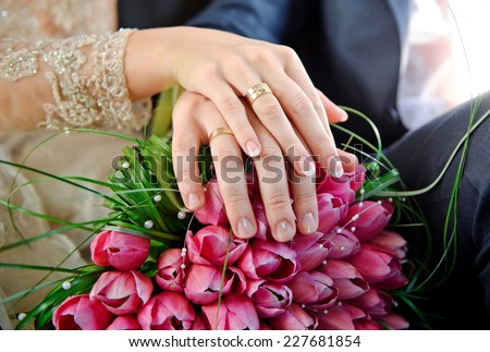 Hands with rings bride and groom on the wedding bouquet of pink tulips.