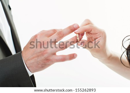 Hands with rings Groom putting golden ring on bride\'s finger during wedding ceremony Loving couple closeup in studio isolated portrait on white background