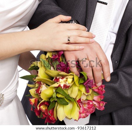 Hands with rings-Hands of bride and groom and rings with wedding bouquet loving couple closeup in studio isolated portrait on white background