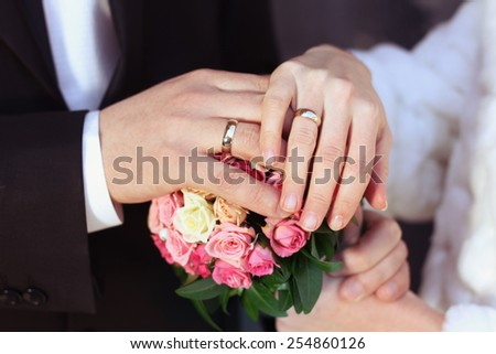 Hands with rings of white gold. Wedding rings. Bride and groom at the wedding. Hands of the bride and groom at a wedding bouquet. Bouquet of roses and hands with rings.